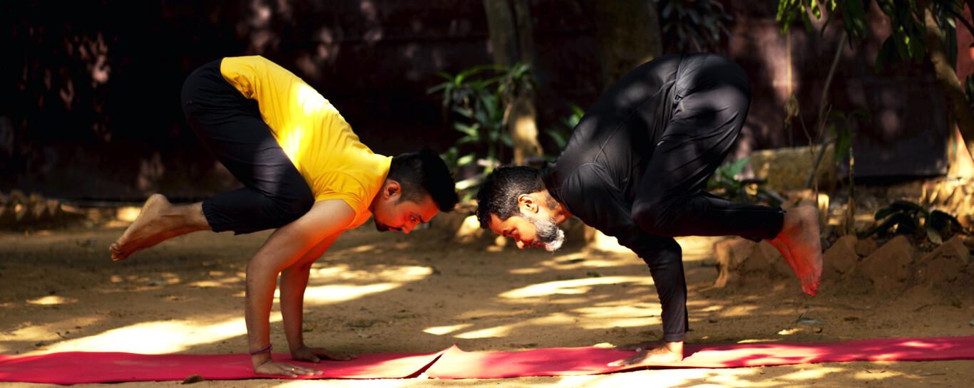 shyam ahir and dinesh chengappa doing the bakasana or crow yoga pose at srikrishana wellness yoga centre