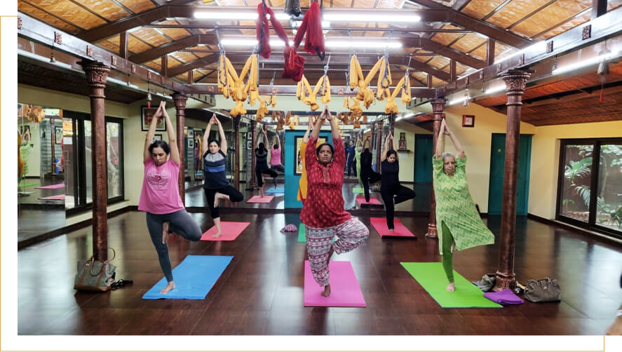 Vriksasana or the Tree Pose yoga posture teaches balance while toning the muscles of the legs demonstrated by ladies of our Yoga classes at Malleshwaram, Bangalore